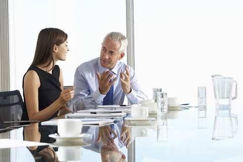 Two Business Colleagues Sitting Around Boardroom Table