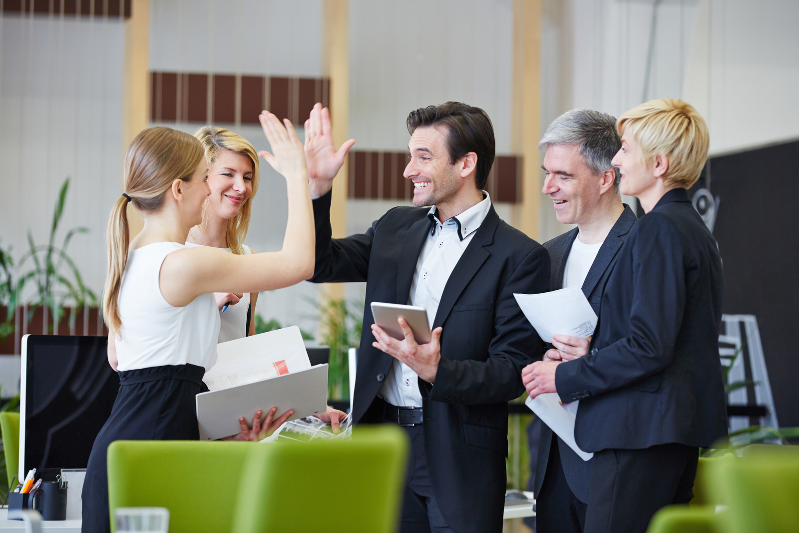 Successful team of business people giving high five in the offic